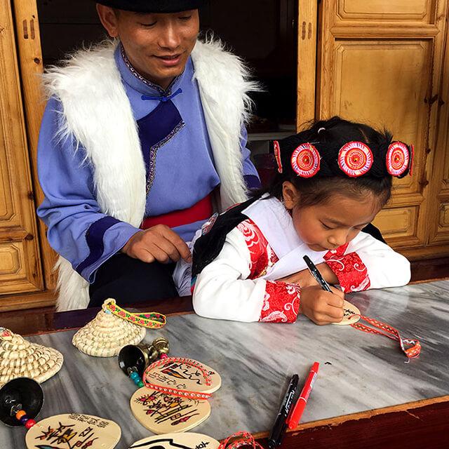 Một cô bé người Naxi đang ghi điều ước của mình lên tấm gỗ của chiếc chuông gió