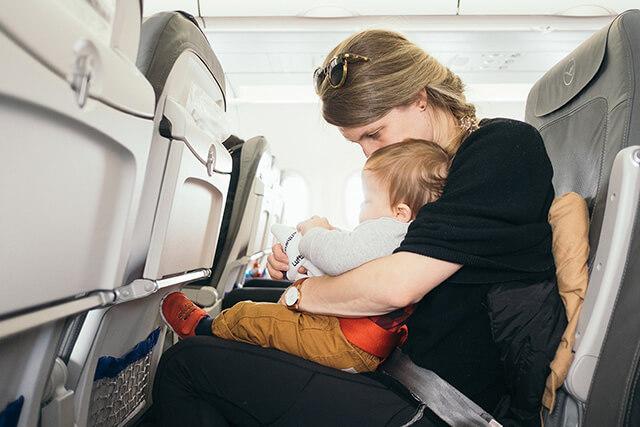 Nếu trẻ còn nhỏ hãy ôm trẻ vào lòng để cùng thắt dây an toàn với cha mẹ trên hành trình bay